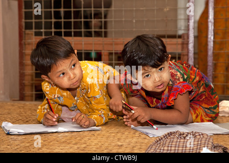 Myanmar, Burma. Bagan. Young Burmese Girls Writing in notebooks. They have thanaka paste, a cosmetic sunscreen, - Stock Photo