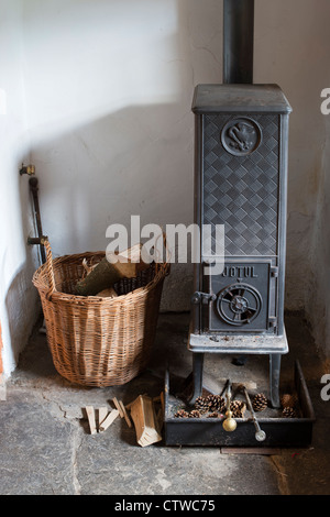 Woodburning stove and a basket of logs in the front room of an english cottage. UK - Stock Photo