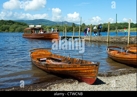 Tourists on a ferry with rowing boats in the foreground on Derwentwater, Keswick in the Lake District, Cumbria - Stock Photo