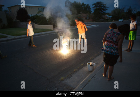 Kids watching dad light fireworks in the street, Southwestern USA. - Stock Photo