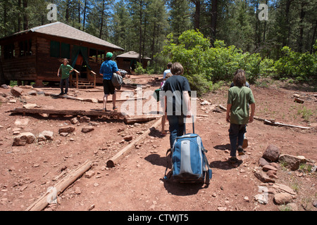 10 - 13 year old boys walking with bags to their cabins at the start of summer camp, Southwestern USA. - Stock Photo