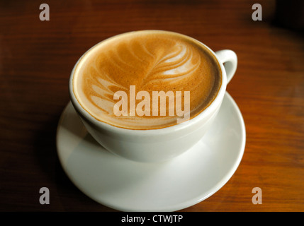 A CUP OF COFFEE , KNOWN IN NEW ZEALAND AS A ' FLAT WHITE '  COMPLETE WITH DESIGN IN THE FROTH COFFEE CUP - Stock Photo