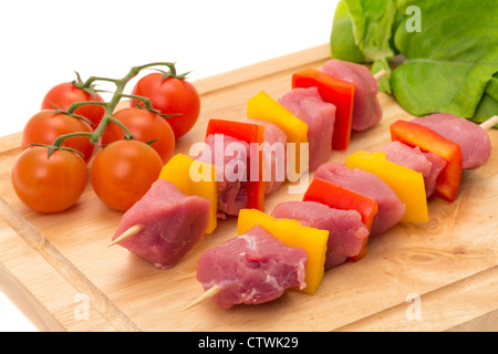 Freshly made pork kebab skewers on a wooden cutting board - studio shot with a white background - Stock Photo