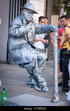 London Covent Gardens Market street entertainer busker mime artist in silver sitting seated on air watched by tourists - Stock Photo