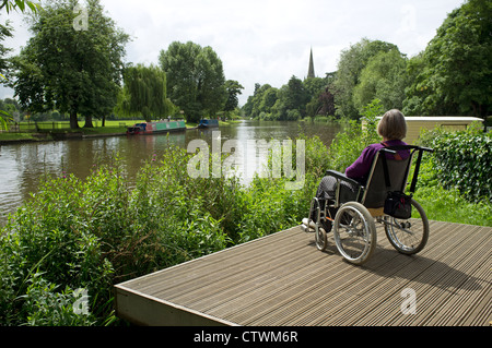 Woman sitting in a wheelchair on the riverside - Stock Photo