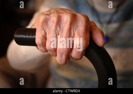 Elderly woman's wrinkled hands clutching a walking stick - Stock Photo