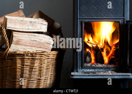 Wood burning in a woodburning stove and a basket of logs. UK - Stock Photo