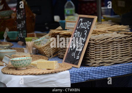 A market stall selling cheese in wicker baskets and checked tablecloth - Stock Photo