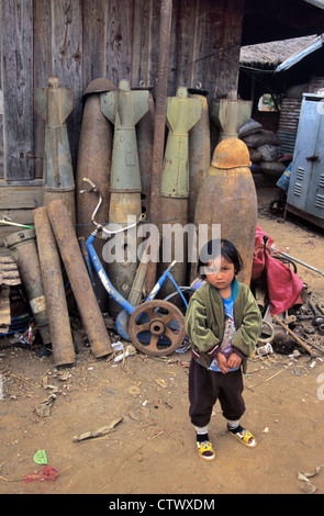 Young Lao or Laotian Girl in Scrap Metal Yard with War Waste Bombs and Missiles from the Vietnam War Phonsavan Laos - Stock Photo