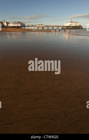 The sandy shore with the pier in the background at Eastbourne, East Sussex, England, UK. At low tide. - Stock Photo