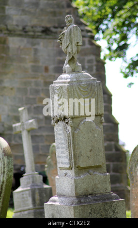 Old gravestone in cemetery with church in background. - Stock Photo