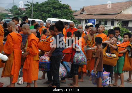Buddhist monks collecting alms during Lent. Luang Brabang. - Stock Photo