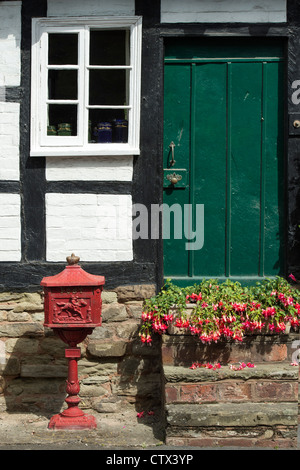 Old historic royal mail post box outside a Black and White English Timber framed building. Pembridge. Herefordshire. - Stock Photo