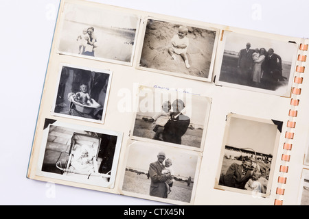 Old faded black and white printed photographs in a family photograph album from 1950s era with page showing photos - Stock Photo