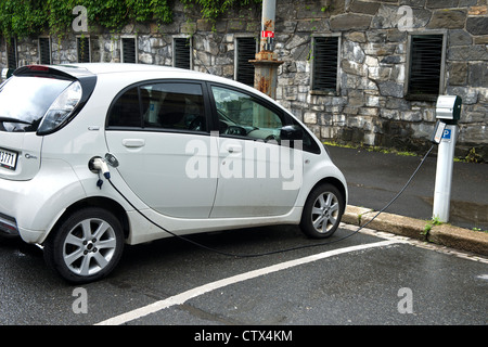 electric car recharging its battery at an electric vehicle charging station in a parking lot in the city centre - Stock Photo