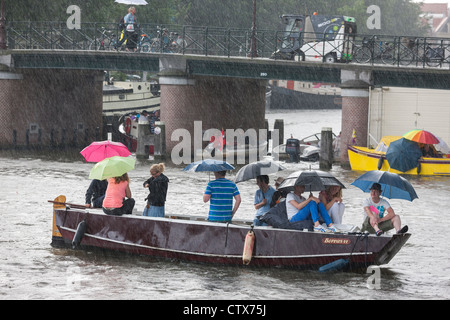 Sudden torrential summer rain in Amsterdam. 9 people in a small boat, sloop, with umbrellas. - Stock Photo