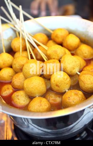 Curry fish balls for sale along the Jonker Walk weekend street market in Chinatown, Melaka. - Stock Photo