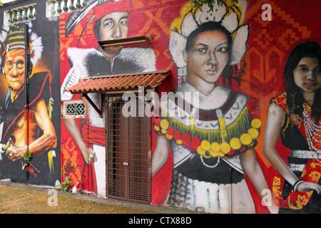 Mural on side of building depicting indigenous tribes of Malaysia. Melaka River, Melaka - Stock Photo