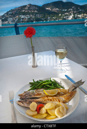 Alfresco restaurant table setting with fresh local simple rustic fish lunch in Puerto Andratx Mallorca Balearic - Stock Photo