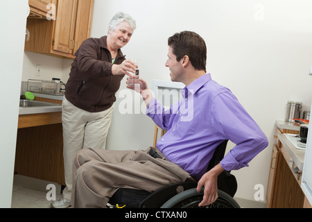 Home health aid offering a glass of water to a man in wheelchair with spinal cord injury - Stock Photo