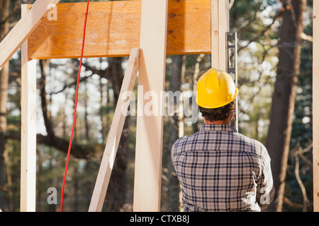 Carpenter using a level on framing - Stock Photo