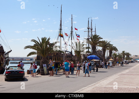 Quay with walking tourists and old stylized ships in the port of city of Sousse, Tunisia, Africa - Stock Photo