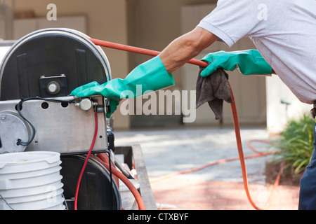 Pest control technician pulling hose from reel in service truck - Stock Photo