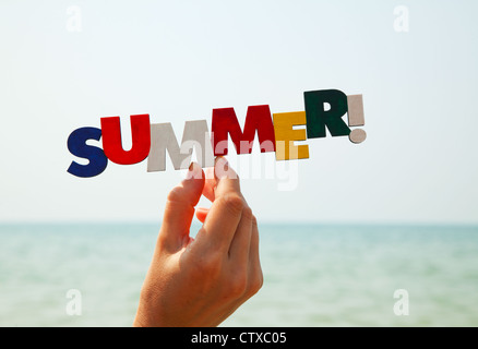 Female's hand holding colorful word 'Summer' against sea in daylight - Stock Photo