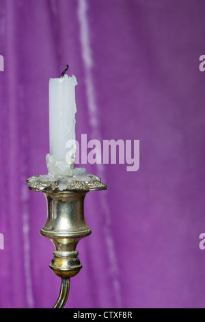 Candle in an old candle stick in front of a purple drape - Stock Photo
