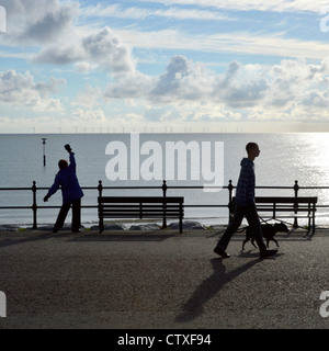 Person exercising on Llandudno Promenade early morning summertime with man walking his dog - Stock Photo