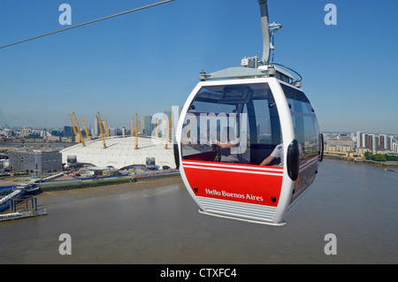 Emirates Air Line sponsored cable car gondola with Hello Buenos Aires advertising on red panel crossing River Thames - Stock Photo