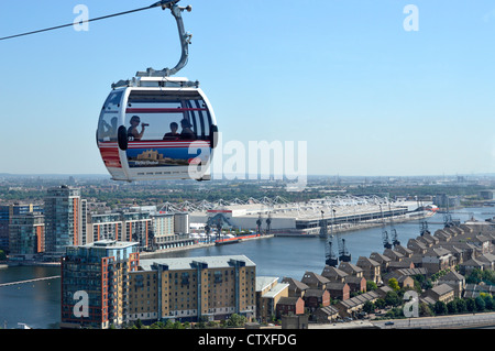 Emirates Air Line sponsored cable car cabin & passengers with Royal Docks and white Excel centre below - Stock Photo