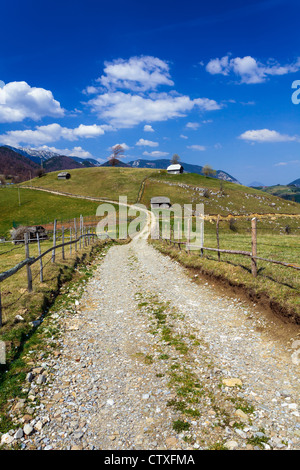Landscape with a rural dirt road in the mountains under sky with fluffy clouds - Stock Photo