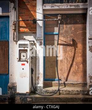 Old defunct petrol pump outside redundant premises - Stock Photo