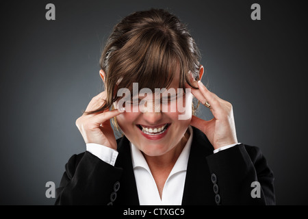 Young businesswoman with strong migraine - Stock Photo