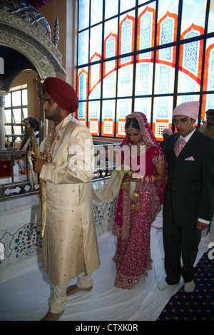 Sikh wedding rituals with the husband and wife-to-be holding the scarf - Stock Photo