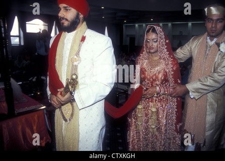 Sikh husband and wife walk around the altar. She holds the traditional scarf and is assisted by her brother - Stock Photo