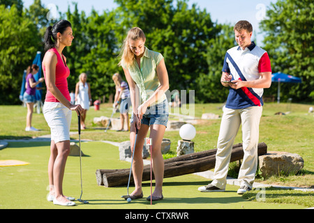 People, man and women, playing miniature golf on a beautiful summer day - Stock Photo