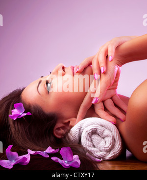 Beautiful relaxing female in spa salon, cute brunette girl with purple flowers in hair isolated on pink background - Stock Photo