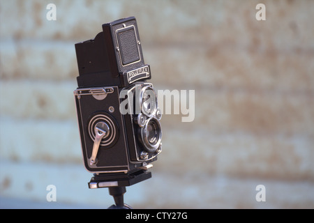 An old Rolleiflex camera against a pale blue distressed background. - Stock Photo