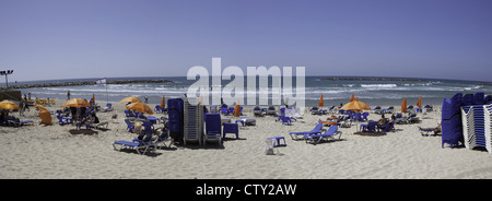Beach chairs and people relaxing along the coast in Tel Aviv, Israel - Stock Photo