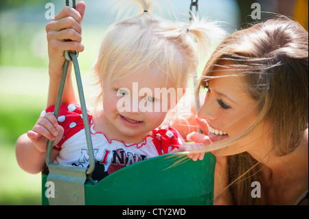 Young mother with two years old female child on a swing in a park - Stock Photo