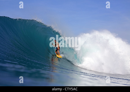 Australian surfer surfing a large green wave on a remote tropical island off North Sumatra, Indonesia. - Stock Photo
