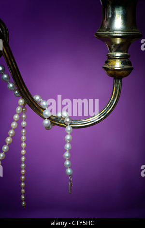 Pearl necklace on an old candle stick in front of a purple drape - Stock Photo