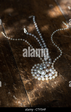 Pearl necklace on old oak floor boards in the sunlight - Stock Photo