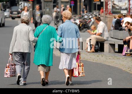 Antwerp / Antwerpen, Belgium. Three old women walking arm in arm - Stock Photo