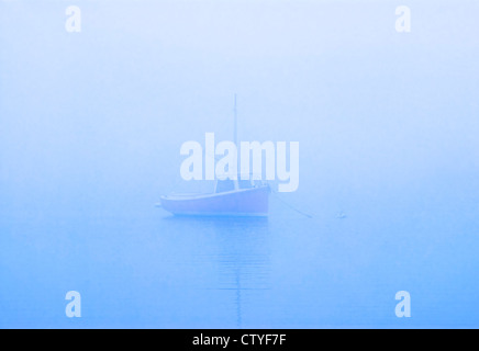 Lone boat on misty still water, Osterville, Cape Cod, MA - Stock Photo