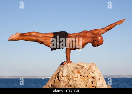 balance strong man balancing on rock. - Stock Photo