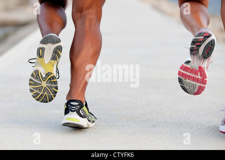 feet of fit healthy couple in jogging or running training session - Stock Photo