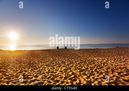 Sun comes over the horizon on a Maine beach in summer - Stock Photo
